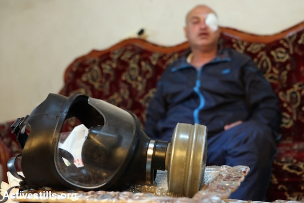 Palestinian photojournalist Nidal Ashtiyeh displays his gas mask at his home in the village of Salem, West Bank, May 16, 2015. A rubber bullet fired by Israeli troops at a Nakba Day protest near Nablus struck the glass of his mask, which shattered and wounded his eye. (Ahmad Al-Bazz/Activestills.org)