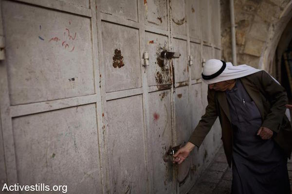 "A Palestinian shopkeeper locks his store to prevent it from being attacked, shortly before Israeli nationalists enter the area in the ""March of the Flags"", Damascus Gate, East Jerusalem, May 20, 2012. (Oren Ziv/Activestills.org)"