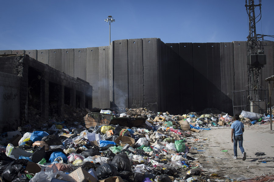 Garbage collects near the separation wall in the Shuafat Refugee Camp inside Jerusalem's municipal boundaries, November 19, 2014. Despite being inside Jerusalem, the city does not provide municipal services like trash collection to neighborhoods beyond the concrete barrier. (Activestills.org)