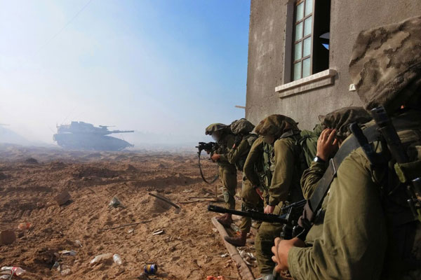 Israeli soldiers take cover along the side of a home in the Gaza Strip during 2014's Operation Protective Edge. (Courtesy of Breaking the Silence)