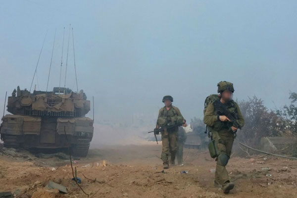 An Israeli soldiers walk next to a tank in the Gaza Strip during 2014's Operation Protective Edge. (Courtesy of Breaking the Silence)