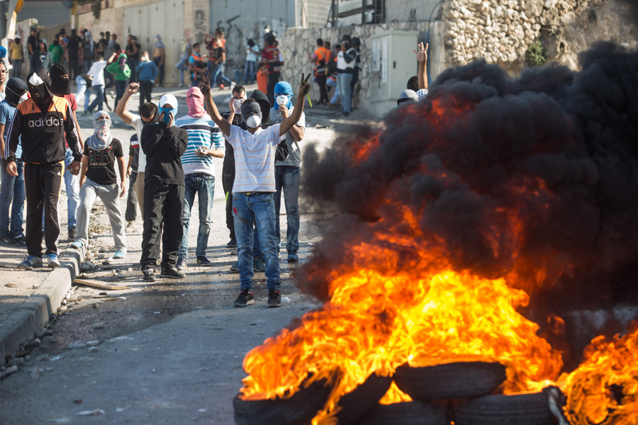 Palestinian youth burn tires during clashes with Israeli police in the East Jerusalem neighborhood of Issawiya, October 24, 2014. (Activestills.org)