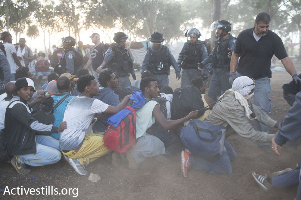 African asylum seekers hold onto one another in hopes of stopping Israeli riot police, seen in the background, from taking them back to the Holot detention facility.