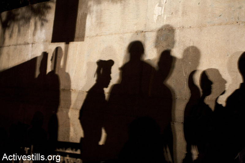 Shadows of protesters and border policemen in front of the house of the finance minster, Yair Lapid, during a demonstration against privatization of natural gas found in the Mediterranean sea, Tel Aviv, June 15, 2013. The protesters demonstrated in front of the minister's house and marched through his neighborhood, blocking several main roads. (Keren Manor/Activestills.org)