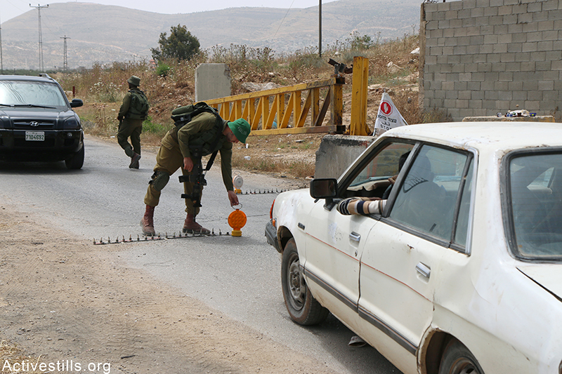 Israeli soldiers check Palestinian cars at Beit Furik checkpoint, near Nablus, West Bank, May 27, 2015. Ahmad al-Bazz / Activestills.org