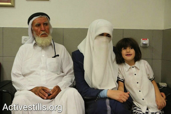 Khader Adnan's father (left), wife (center) and daughter (right) wait outside his room at Assaf Harofeh Hospital, Israel, June 29, 2015. (photo: Yotam Ronen/Activestills.org)