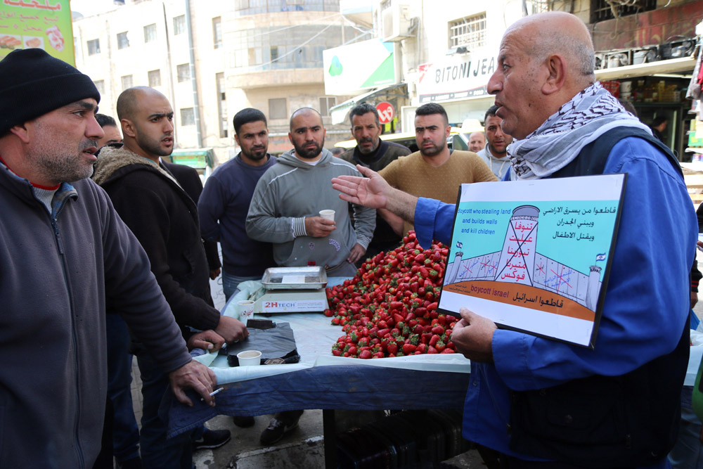 A Palestinian boycott activist canvasses in the Ramallah open market, explaining the boycott of Israeli goods to Palestinian merchants, March 17, 2015. (Activestills.org)