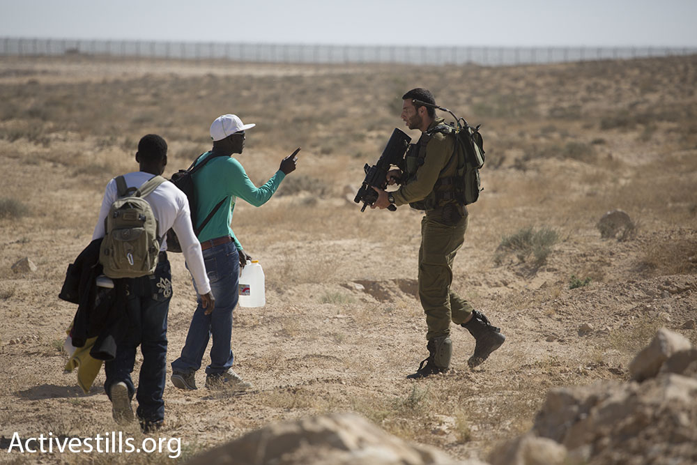 An Israeli soldier stops asylum seekers from approaching the Egyptian border.