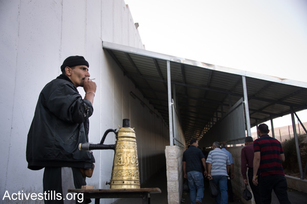 A Palestinian vendor sells coffee outside the entrance to an Israeli military checkpoint separating Bethlehem and Jerusalem, June 12, 2014. (Activestills.org)