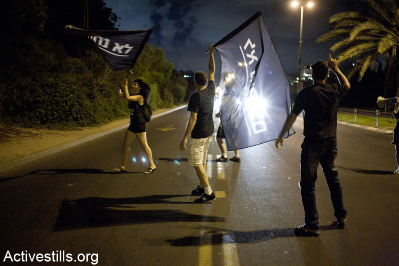 Activists block Ayalon high-way in Tel Aviv during a demonstration against privatization of natural gas found in the Mediterranean sea, June 15, 2013. The protesters demonstrated in front of the home of the finance minster, Yair Lapid and marched through his neighborhood, blocking several main roads. (Keren Manor/Activestills.org)