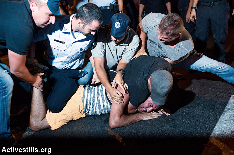 Police arrest a protester during a protest against natural gas privatisation in Tel Aviv, June 27, 2015. Four protestors were arrested during the demonstration. (Yotam Ronen/Activestills.org)