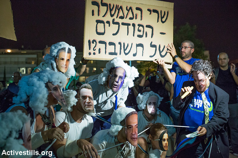 "Protester illustrating government weakens regarding energy companies during a protest against natural gas privatisation in Tel Aviv, June 27, 2015. Sign reads: ""The government ministers - the poodle of Tshuva?"" (Yotam Ronen/Activestills.org)"