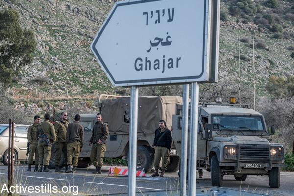 Israeli soldiers stand near the entrance to the divided village of Ghajar on the Lebanese-Israeli border, January 19, 2015. (Yotam Ronen/Activestills.org)
