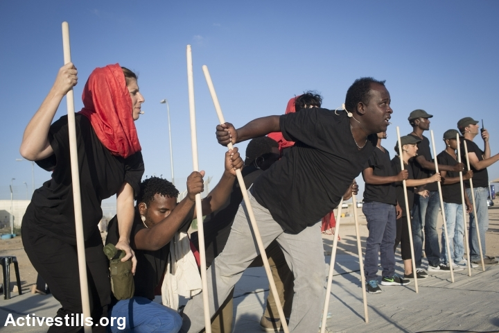 Israelis and African Asylum seekers jailed in Holot preform during a theatre show outside the Holot detention center in the Negev desert, June 13, 2015. (photo: Oren Ziv/Activestills.org)