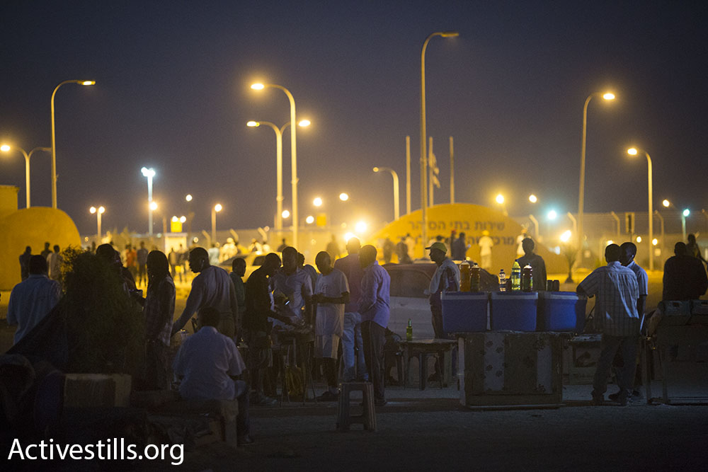 Detainees at Holot eat dinner at makeshift restaurants outside the detention facility's gates. The restaurants are the initiatives of entrepreneurial detainees.