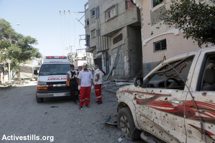 Medics take cover from shooting in the Shujaiyeh area during a short humanitarian ceasefire, Gaza City, July 23, 2014. The medics and journalists came under fire and were forced to withdraw from the area after a short time. Shujaiyeh was been heavily bombed by Israel in heavy fighting and shelling that left roughly 100 Palestinians dead. Thirteen Israeli soldiers were killed in the fighting. (Ann Paq/Activestills.org)