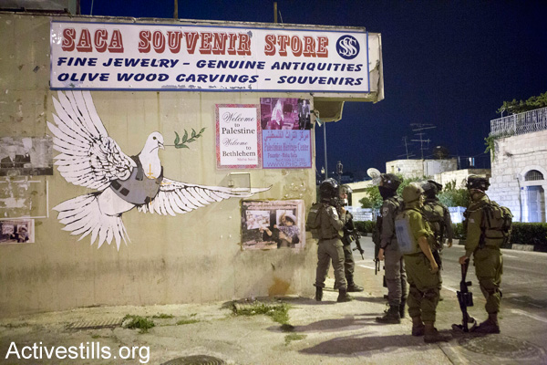 Israeli soldiers stand outside a souvenir shop for tourists in Bethlehem, July 12, 2014. (Activestills.org)