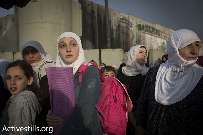Holding on to a yoga mat in line at Qalandiya checkpoint during the second Friday of Ramadan, June 26, 2015. (photo: Oren Ziv/Activestills.org)