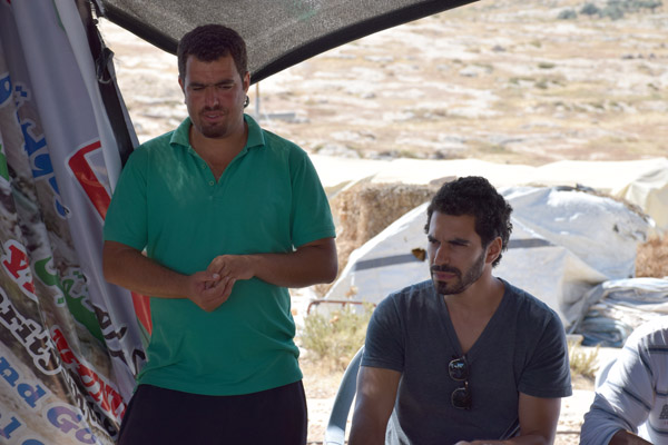 Nasser (left) speaks to members of All That's Left as Yuval, a member of the group, translates from Arabic to English, June 13, 2015. (Photo by Michael Schaeffer Omer-Man)