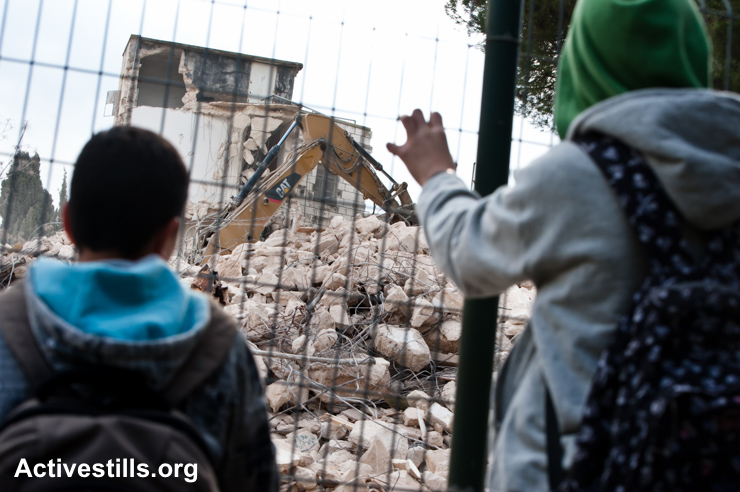 Palestinian children watch as a Caterpillar digging machine demolishes a Palestinian property in Sheikh Jarrah to make way for new Israeli settlements in East Jerusalem, January 9, 2011. (photo: Ryan Rodrick Beiler/Activestills.org)