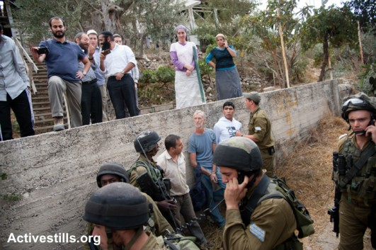 As Israeli settlers look on from above, Israeli soldiers arrest two Palestinians and an international solidarity activist after settlers interfered with a Palestinian family harvesting olives, Hebron, West Bank, October 22, 2012. (Activestills)