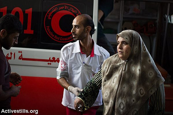 Palestinians injured in Israeli air strikes on the Gaza Strip arrive at Al Shifa Hospital in Gaza City on the night of July 8, 2014. On the first day of the Israeli offensive 23 Palestinians were killed, including 7 children, and about 320 were injured. (Basel Yazouri/Activestills.org)