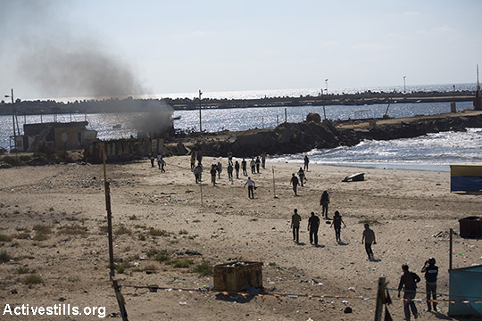 Smoke rises from Gaza shore after missiles launched by the Israeli navy killedfourchildren from the Bakr family whowere playing on the beach, July 16, 2014. (Anne Paq/Activestills.org)