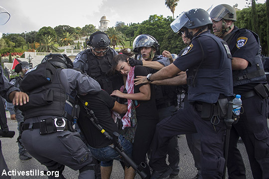 Israeli policemen arrest protesters as Palestnians living in Israel and left wing activists protest against the Israeli attack on Gaza in down town Haifa, July 18, 2014. Israeli police arrested 28 activists, as protesters took the streets and blocked roads calling to put an end to the attack. (Faiz Abu Rmeleh/Activestills.org)