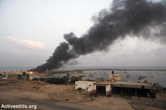 Smoke rises above the sea port of Gaza City following Israeli airstrikes, Gaza City, July 29, 2014. (Anne Paq/Activestills.org)