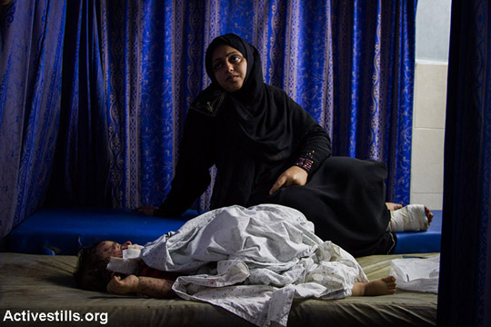 An injured Palestinian child awaits treatment at Al Shifa Hospital in Gaza City following Israeli attacks, July 30, 2014. (Basel Yazouri/Activestills.org)