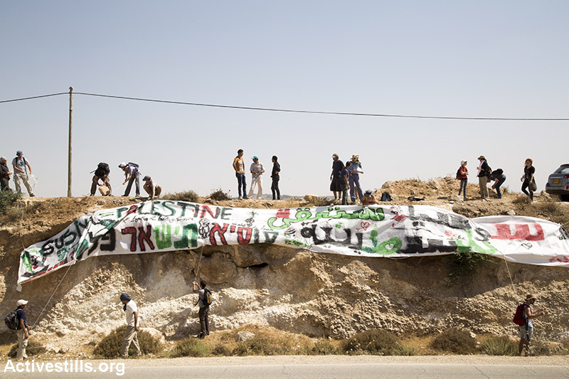 Activists hang a massive sign on the main road leading to the former site of the village, to ensure that Israeli settlers see it, July 24, 2015. (Keren Manor/Activestills.org)