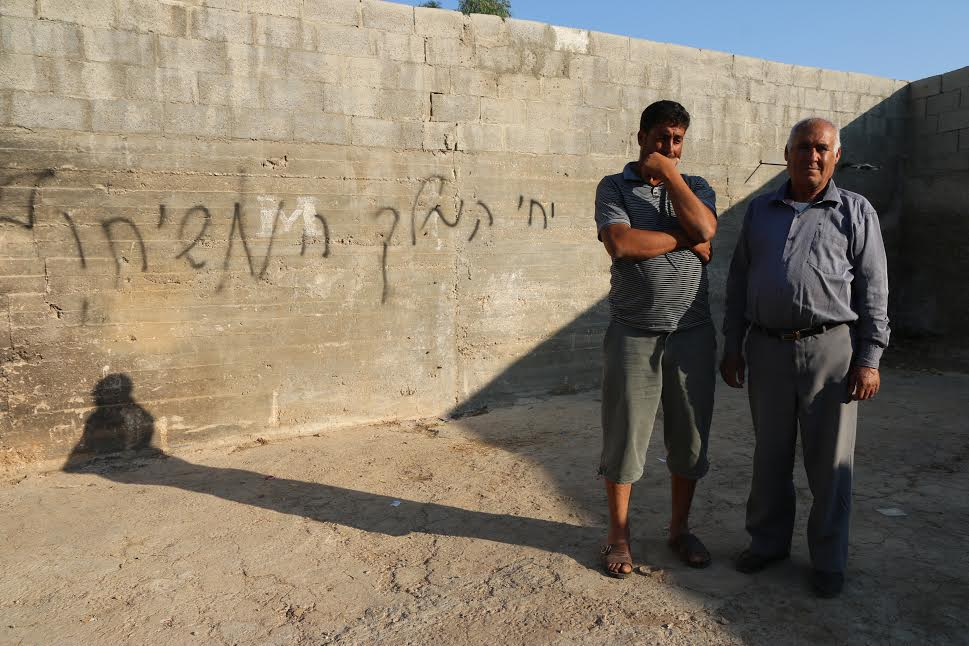 Palestinian relatives of 1.5-year-old Ali Saad Dawabsha stand outside the family home that was attacked by Israeli settlers overnight. The graffiti reads: 'Long live the Messiah,' Douma, West Bank, July 31, 2015. (photo: Ahmad Al-Bazz/Activestills.org)