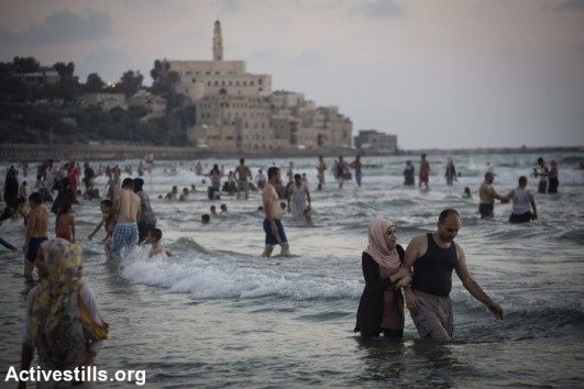 Palestinians from the West Bank enjoy the Mediterranean Sea on the last day of the Eid-al-Fitr holiday, in Tel Aviv, August 11, 2013. The three-day Eid al-Fitr holiday marks the end of the holy fasting month of Ramadan. (photo: Oren Ziv/Activestills.org)