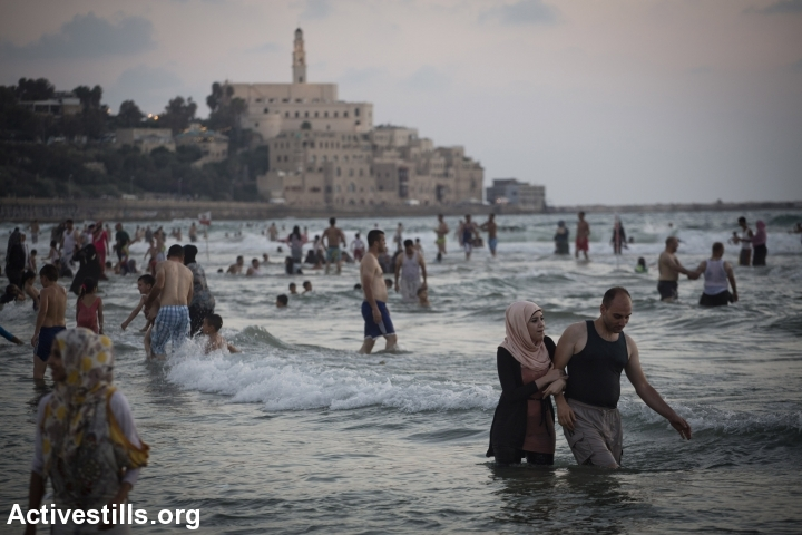 Palestinians from the West Bank enjoy the Mediterranean Sea on the last day of the Eid-al-Fitr holiday, in Tel Aviv, August 11, 2013. The three-day Eid al-Fitr holiday marks the end of the holy fasting month of Ramadan. (photo: Oren Ziv/Activestills.org)