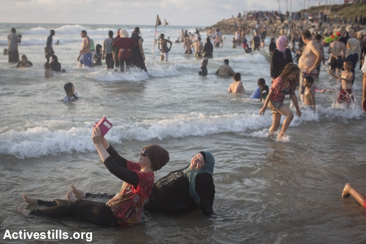 Palestinian women take a 'selfie' on the beach in Tel Aviv during the Eid al-Fitr holiday. (photo: Oren Ziv/Activestills.org)