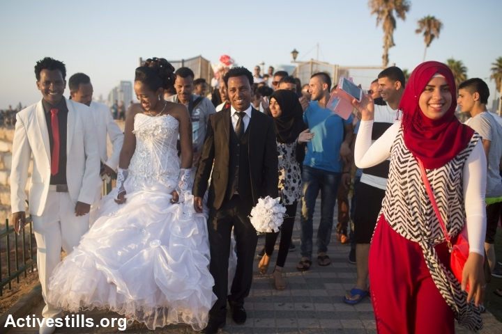 A Palestinian youth takes photos with her cell phone of Eritrean African Asylum seekers on their wedding day in the Mediterranean Sea during the second day of the Eid al-Fitr holiday as the sun sets in Tel Aviv, Israel, Friday, July 18, 2015. (photo: Oren Ziv/Activestills.org)