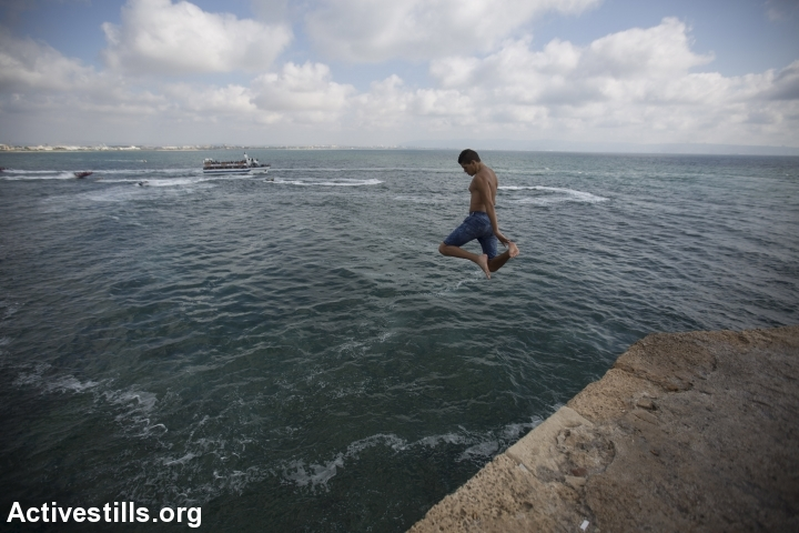 A Palestinian boy jumps to the sea in the city of Acre, during the last day of the Eid al-Fitr, July 19, 2015. (photo: Faiz Abu Rmeleh/Activestills.org)