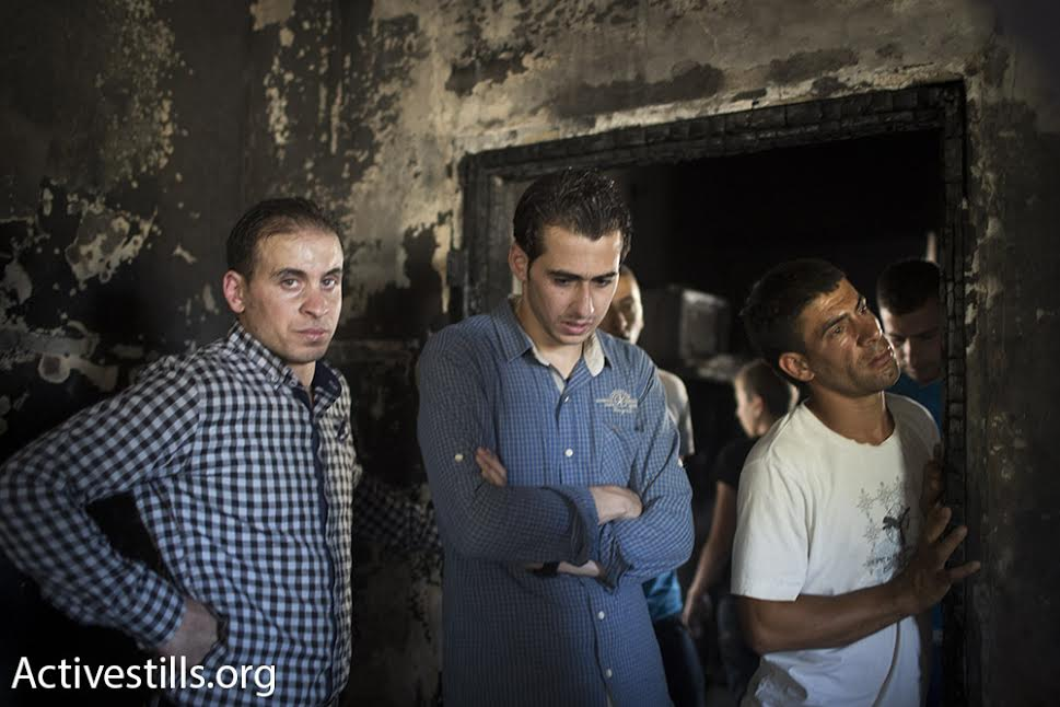 Dozens of people, locals, journalists, and human rights workers, gathered throughout the day in the Dawabshe house, which was set on fire during the early hours of Friday morning, Duma, West Bank, July 31, 2015. (photo: Oren Ziv/Activestills.org)