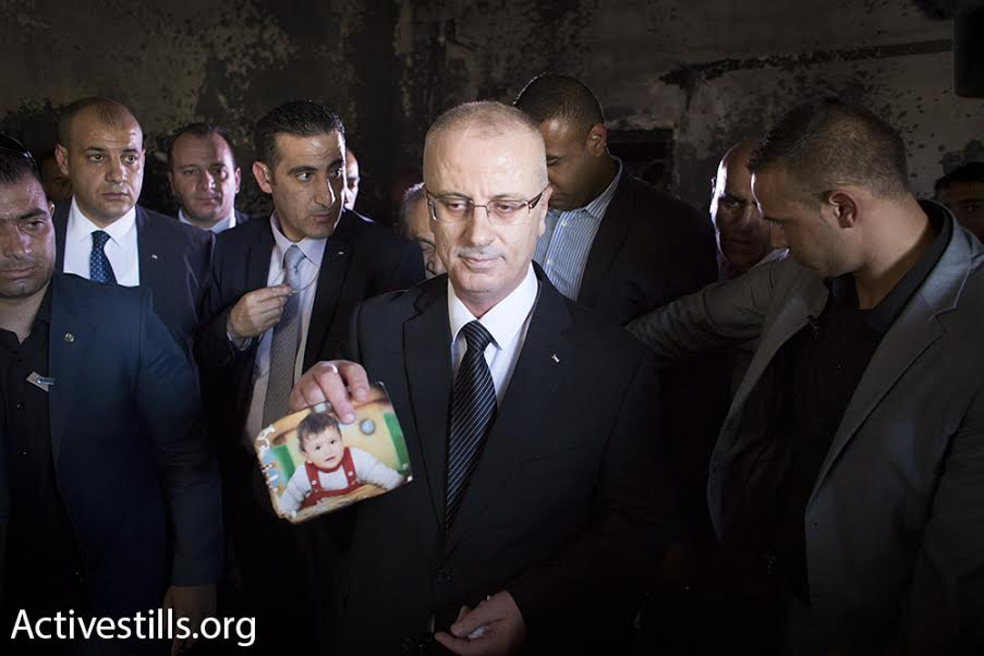 Palestinian Prime Minister Rami Hamdallah holds up a photo of slain Palestinian toddler, Ali Saad Dawabshe, Duma, West Bank, July 31, 2015. (photo: Oren Ziv/Activestills.org)
