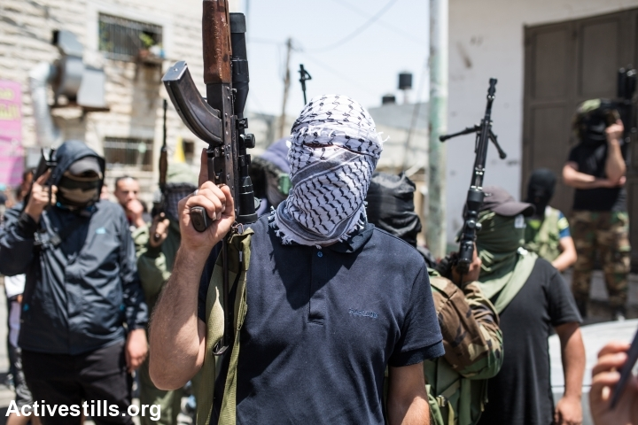 Palestinian militants take part in the funeral of Palestinian youth Mohammed Sami al-Ksbeh, 17, in Qalandiya refugee camp, near the West Bank city of Ramallah July 3, 2015. A senior Israeli army officer shot and killed Ksbeh who was throwing stones near a checkpoint in the West Bank on Friday, June 3, 2015. (photo: Yotam Ronen/Activestills.org)