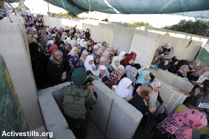 Palestinians cross an Israeli military checkpoint separating the West Bank city of Bethlehem and Jerusalem on their way to pray at the Al-Aqsa Mosque in Jerusalem on the third Friday of the Muslim holy month of Ramadan, July 3, 2015. (photo: Mustafa Bader/Activestills.org)