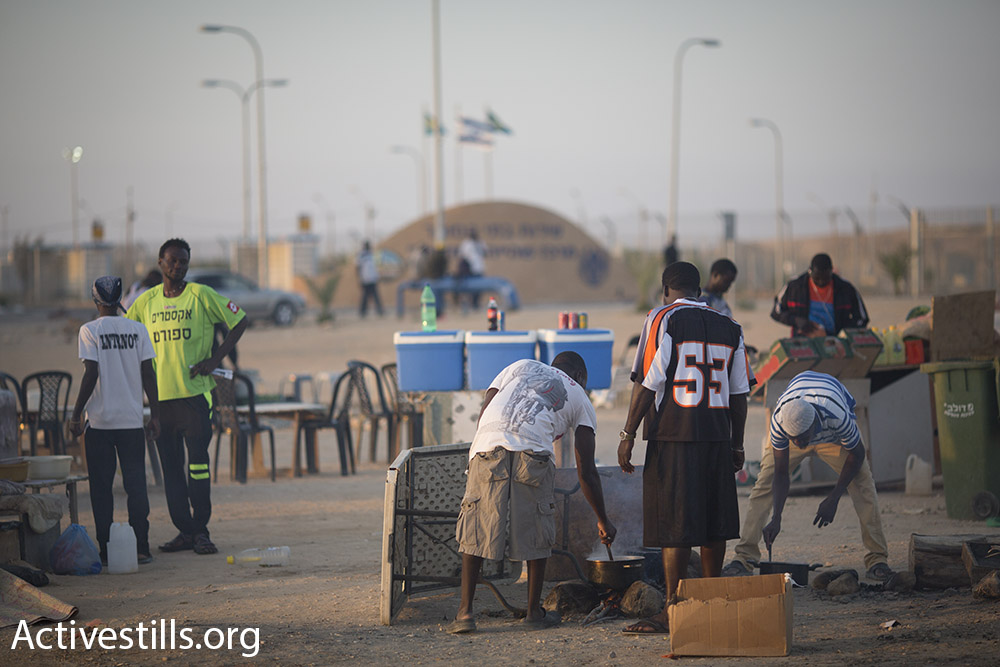 Asylum seekers detainees in Holot have opened some makeshift restaurants outside the prison gates to serve fellow detainees. They are forced to store their supplies in old cars parked nearby because authorities won't allow them to bring any food inside. (Oren Ziv/Activestills.org)