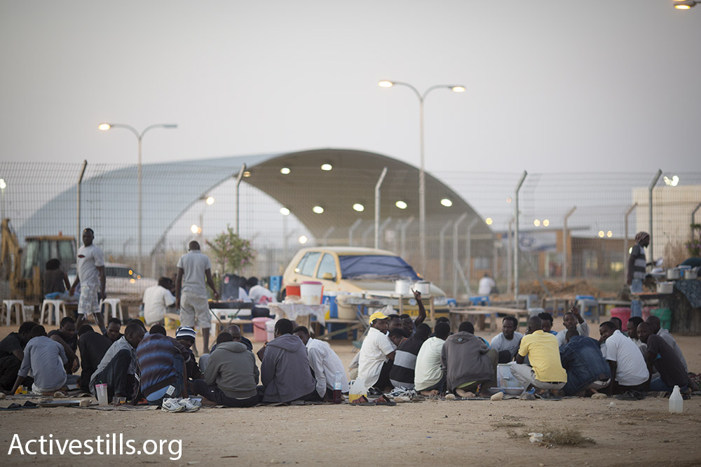 Asylum seekers eat in makeshift restaurants owned by other detainees, outside the Holot detention center's gates, July 2015. (Oren Ziv/Activestills.org)