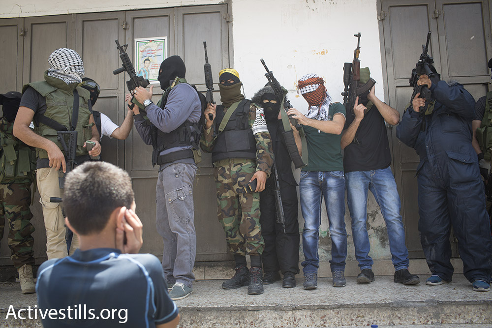 Palestinian youth watch on as militants fire their weapons into the air during the funeral of Muhammad Abu Latifa, July 27, 2015. (Oren Ziv/Activestills.org)