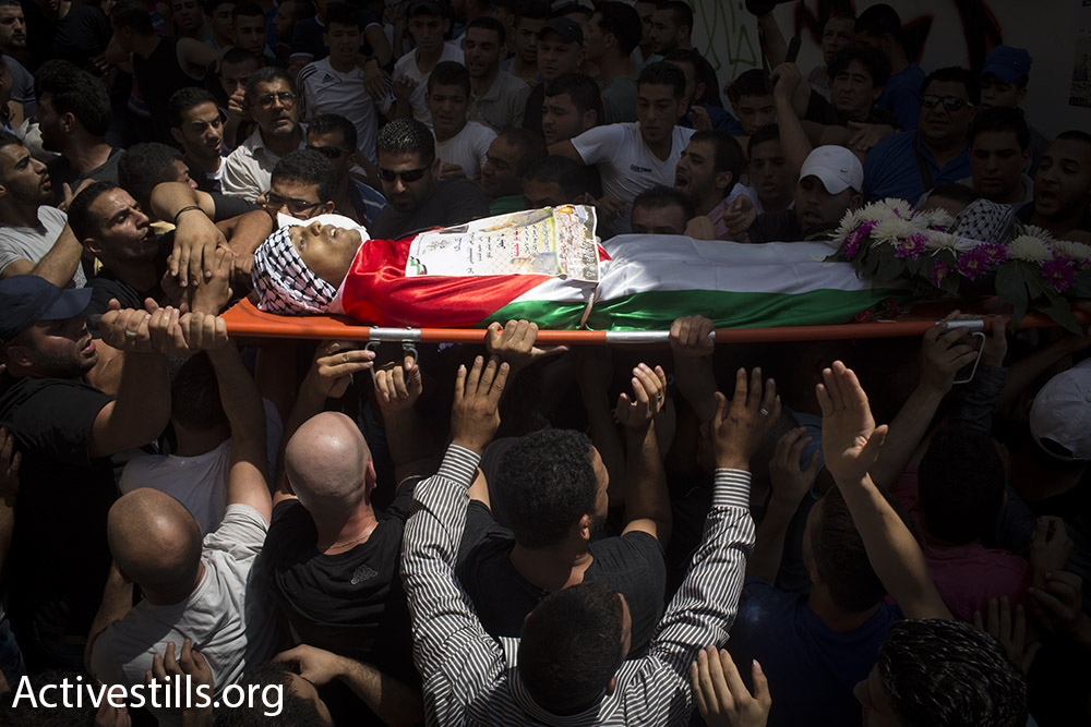 Mourners carry the body of Muhammad Abu Latifa back toward his family home, July 27, 2015. (Oren Ziv/Activestills.org)