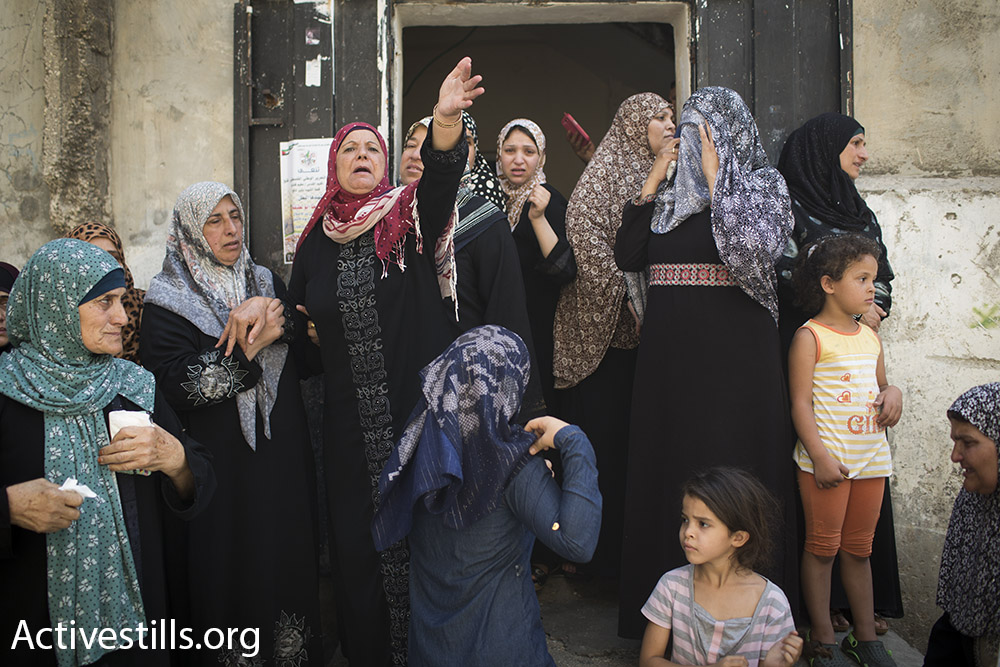 Female family members of Muhammad Abu Latifa mourn outside the family home during his funeral, July 27, 2015. (Oren Ziv/Activestills.org) Abu Latifa was shot and killed by Israeli security forces during a nighttime arrest raid.
