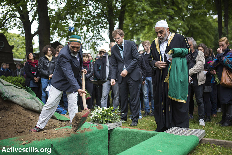 """Activists gather in a cemetery to bury an unidentified migrant from Syria who died in the sea on his way to Europe, Berlin, June 19, 2015. The funeral was held by an Imam as part of a political campaign called """"The Dead are Coming,"""" which is organized by the Center for Political Beauty, a Berlin-based art activist group. The reburial is one of several awareness actions organized by the group. (Activestills.org)"""