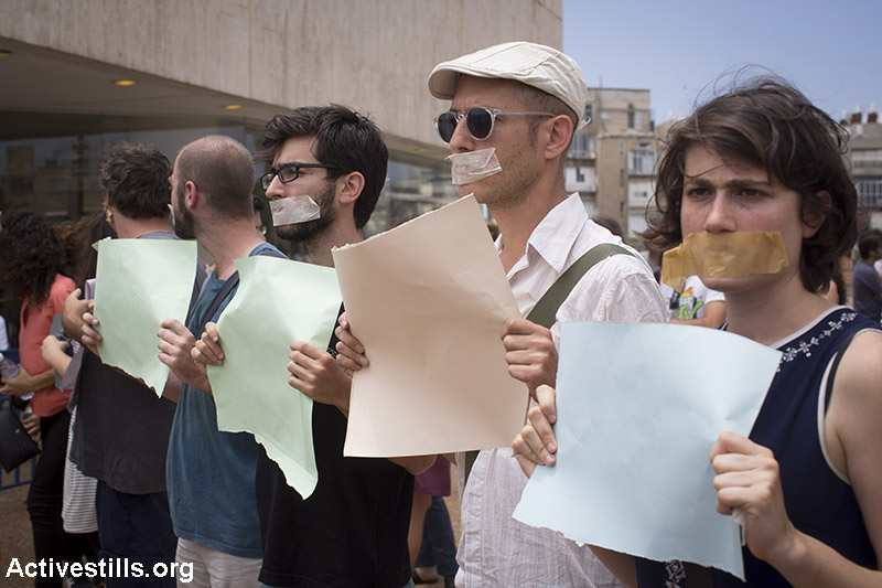Israeli artists wear a tape over their mouths as they take part in a protest against Minister of Sports and Culture Miri Regev (unseen) upon her arrival to a theatre awards ceremony in Tel Aviv,  June 19, 2015. The protest was held after Regev threatened to cut funding for a children's theatre in Jaffa, after it's director, which is also an actor in Haifa theatre, said he will refuse to preform in the West Bank settlement. (Activestills.org)