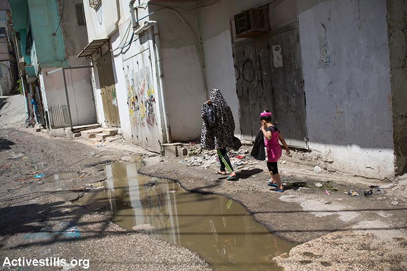 Childran cross an open sewage in the Shu'fat Refugee Camp, East Jerusalem,June 2, 2015. (Activestills.org)