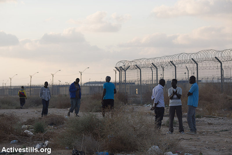 An audience after African asylum seekers jailed in Holot alongside Israelis preformed during a theatre show outside the Holot detention centre in the Negev desert, June 13, 2015. (Activestills.org)
